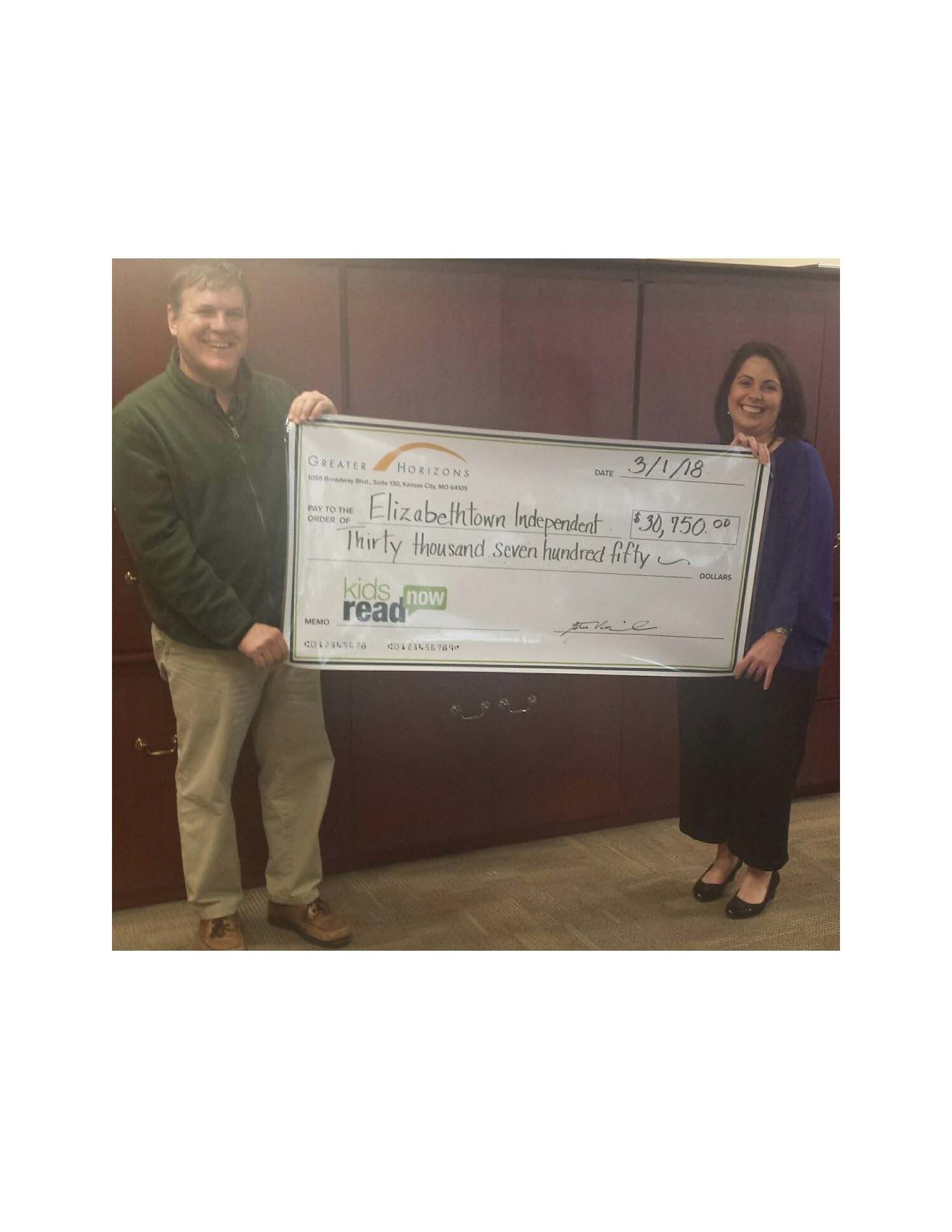 Kelli Bush, Assist. Superintendent Student Learning, receiving check from Steve Marcinak from Kids Read Now